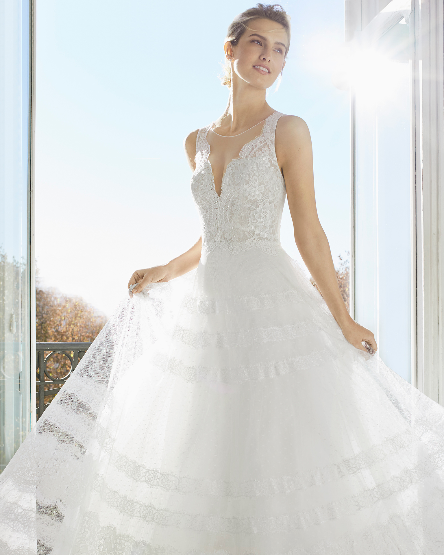 Robe de mariée style trapèze en dentelle et pierreries. Décolleté plongeant et dos en V et transparences. Disponible en couleur naturelle. Collection AIRE BARCELONA 2019.