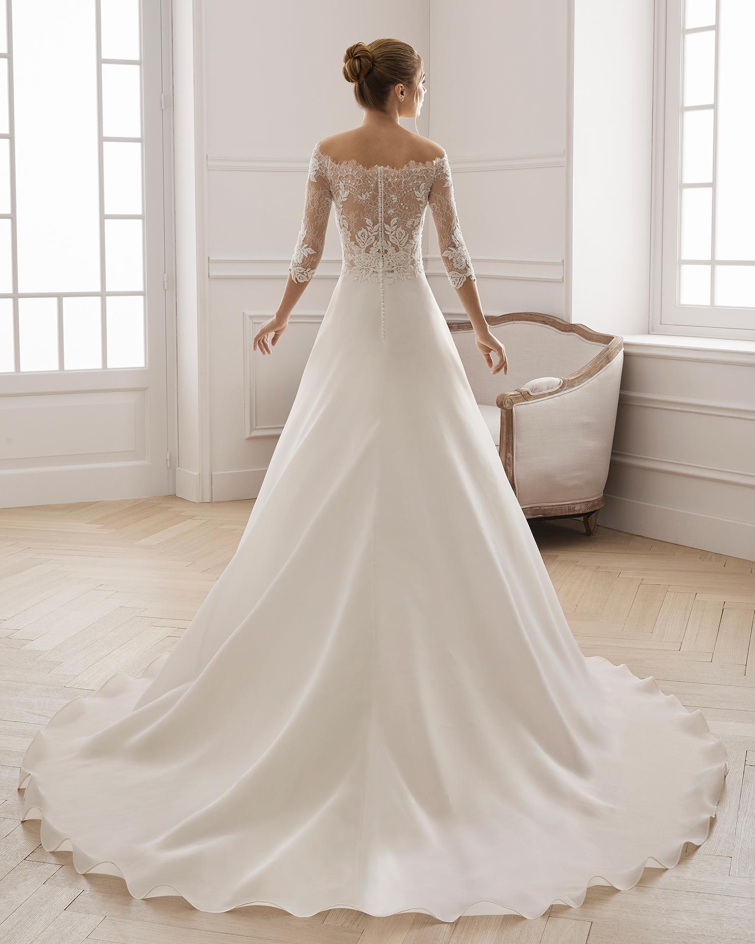 Vestido de novia estilo línea A en gazar y encaje pedrería. Escote barco y manga larga. Disponible en color natural. Colección AIRE BARCELONA 2019.
