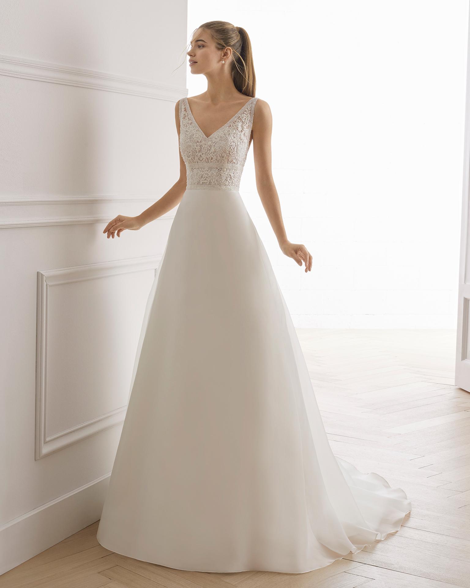 Vestido de noiva estilo linha A de organza e renda de brilhantes. Decote em V e costas descobertas. Disponível em cor natural. Coleção AIRE BARCELONA 2019.