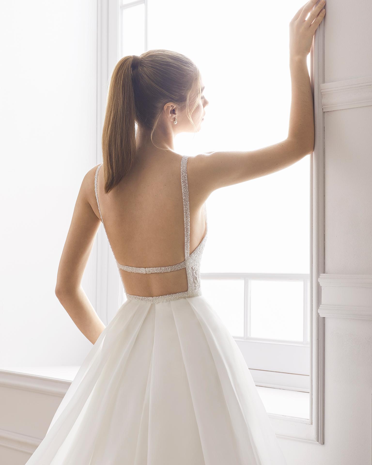 Vestido de novia estilo línea A en organza y encaje pedrería. Escote en V y espalda descubierta. Disponible en color natural. Colección AIRE BARCELONA 2019.