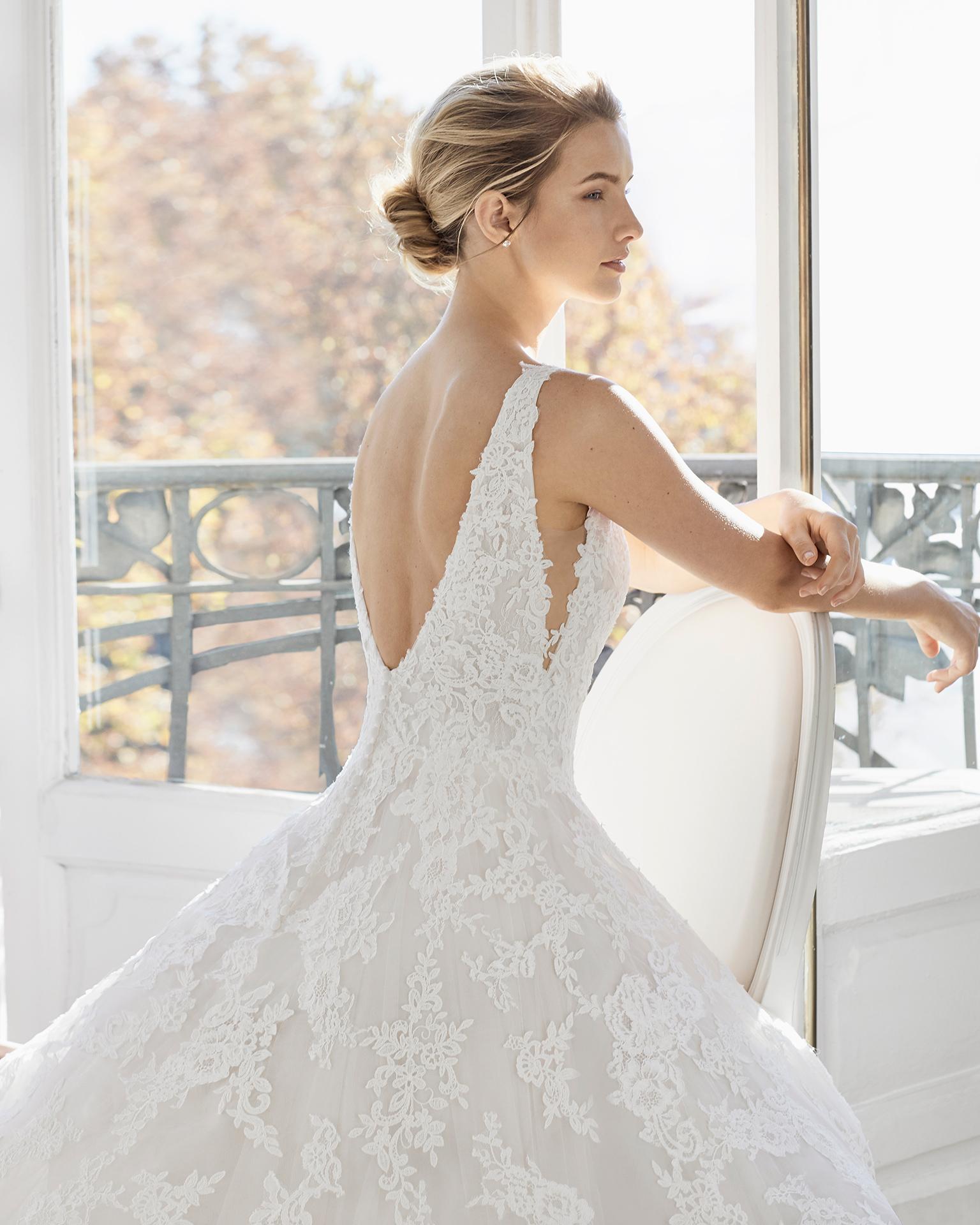 Vestido de noiva estilo romântico de renda. Decote deep-plunge e costas decotadas. Disponível em cor natural/nude. Coleção AIRE BARCELONA 2019.