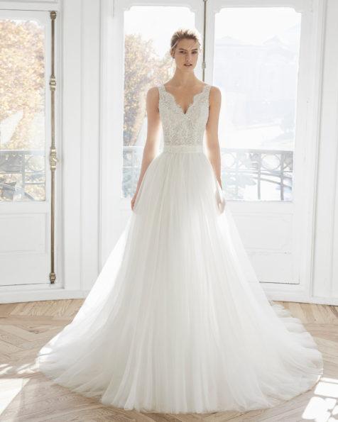 Princess-Brautkleid aus strassbesetzter Spitze und Tüll. V-Ausschnitt, Rücken aus Spitze, abnehmbare Schleppe aus Tüll. Erhältlich in Naturweiß. Kollektion AIRE BARCELONA 2019.