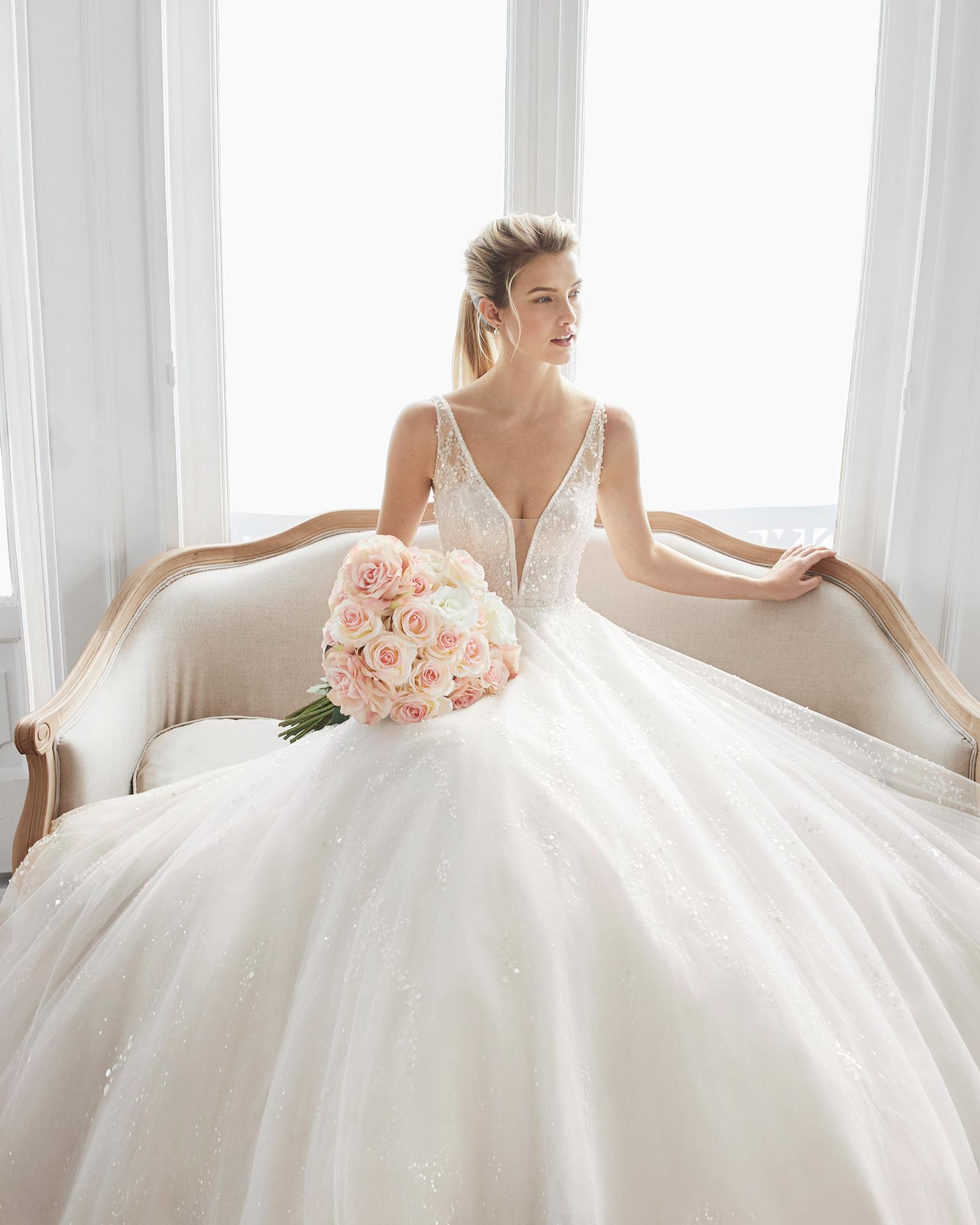 Robe de mariée style princesse en dentelle avec pierreries et tulle. Décolleté plongeant et dos en V. Disponible en couleur naturelle. Collection AIRE BARCELONA 2019.