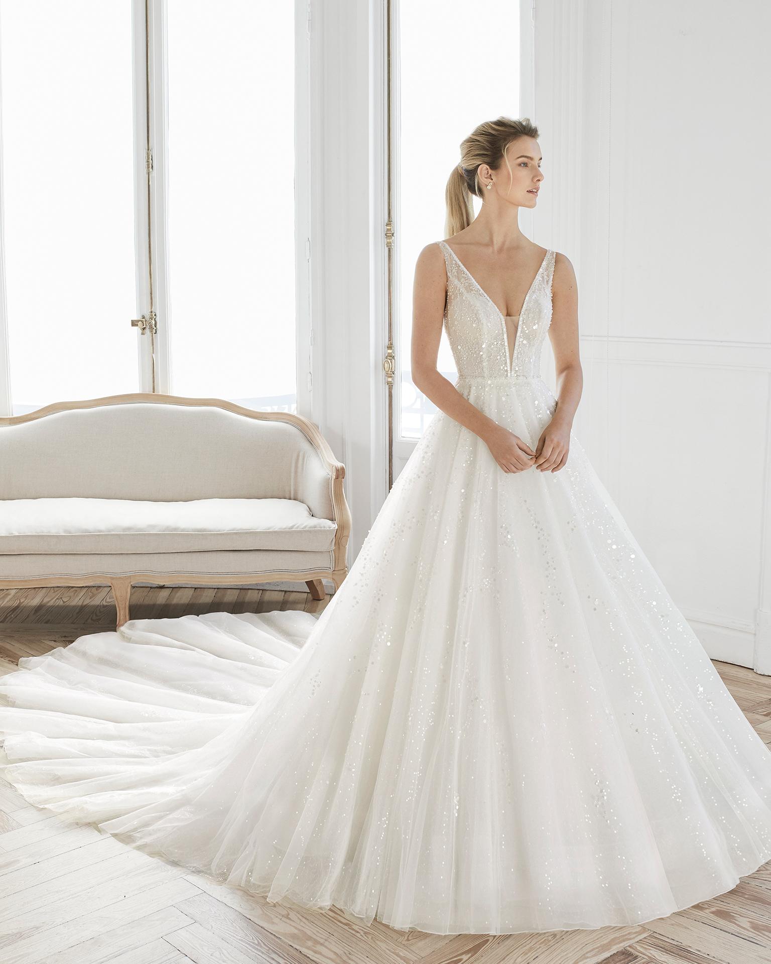 Vestido de novia estilo princesa de encaje pedrería y tul. Escote Deep-plunge y espalda en V. Disponible en color natural. Colección AIRE BARCELONA 2019.