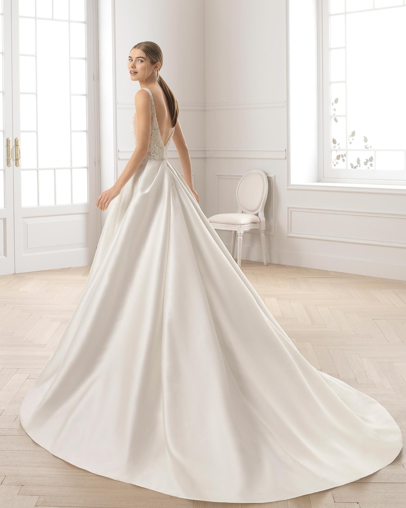 Robe de mariée style trapèze en tamis et dentelle avec pierreries. Col et dos en V. Disponible en couleur naturelle. Collection AIRE BARCELONA 2019.