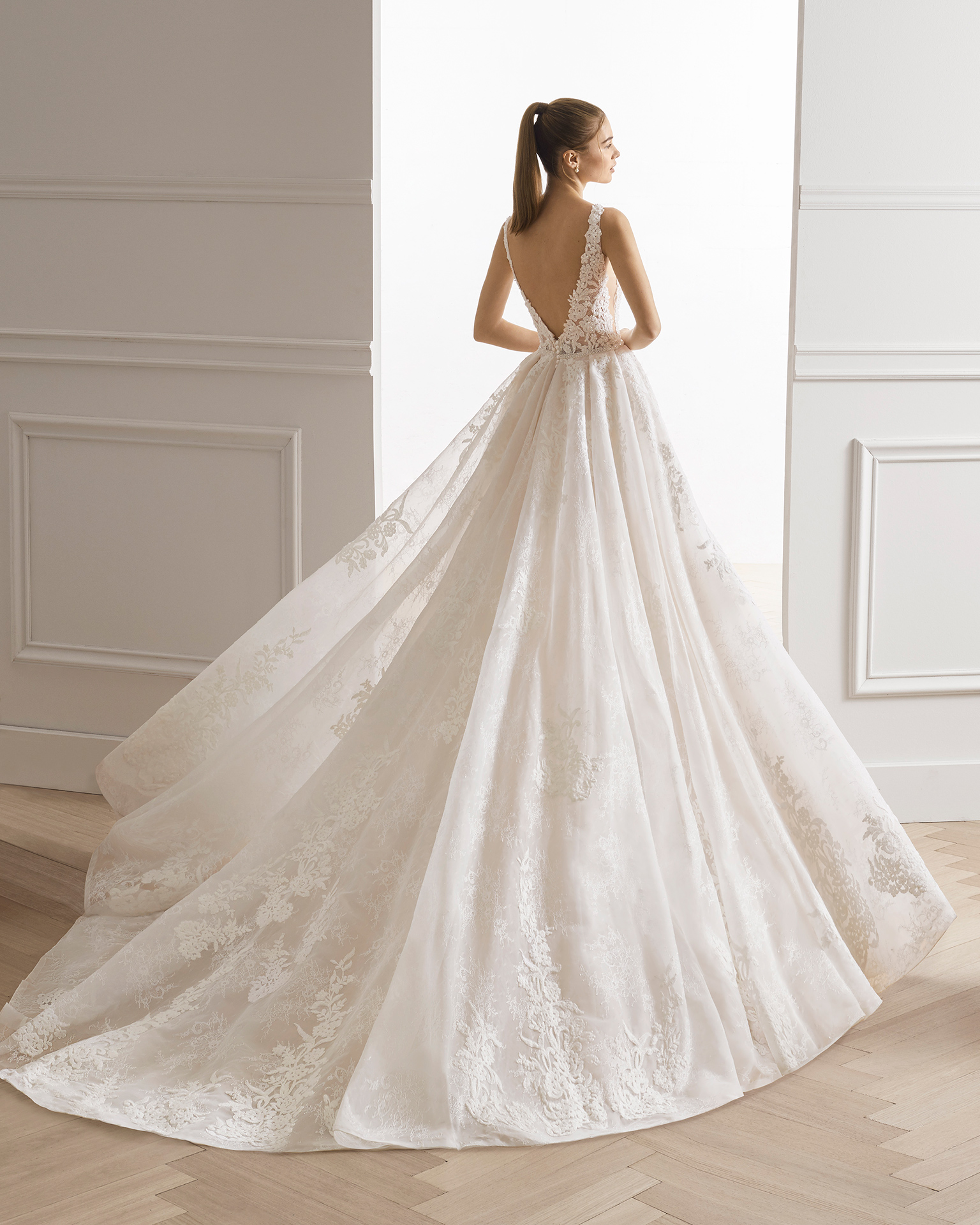 Robe de mariée style princesse en dentelle et pierreries. Col et dos en V avec jupe créant un grand volume. Disponible en couleur naturelle/nude. Collection AIRE BARCELONA 2019.