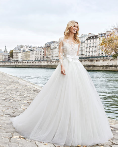 Princess-style beaded lace and tulle wedding dress. Bateau neckline and long sleeves with full skirt. Available in natural. 2019 AIRE BARCELONA Collection.