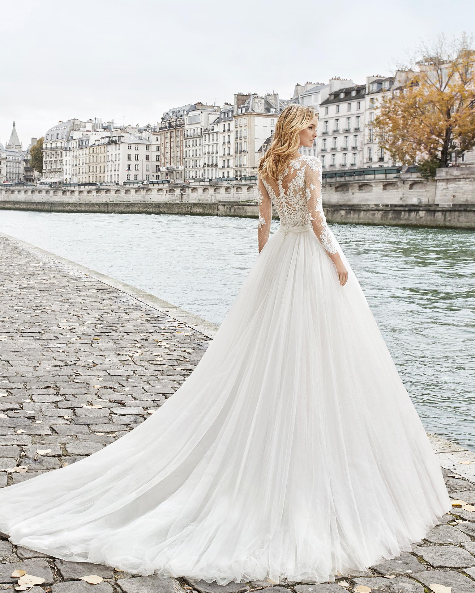 Vestido de noiva estilo princesa de renda, brilhantes e tule. Decote à barco e manga comprida com saia muito volumosa. Disponível em cor natural. Coleção AIRE BARCELONA 2019.