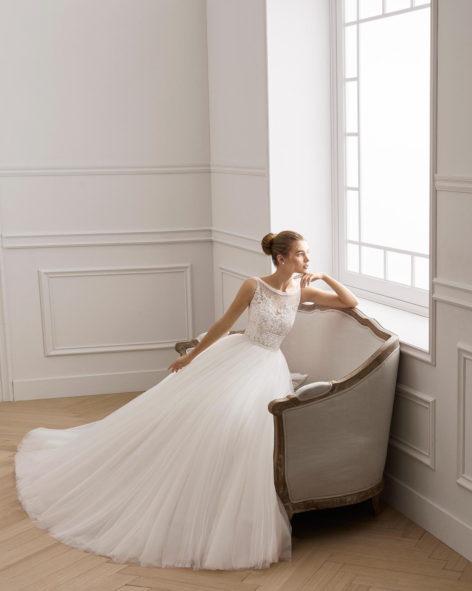 Robe de mariée style princesse en dentelle avec pierreries et tulle doux. Col bateau et décolleté dans le dos. Disponible en couleur ivoire. Collection AIRE BARCELONA 2019.