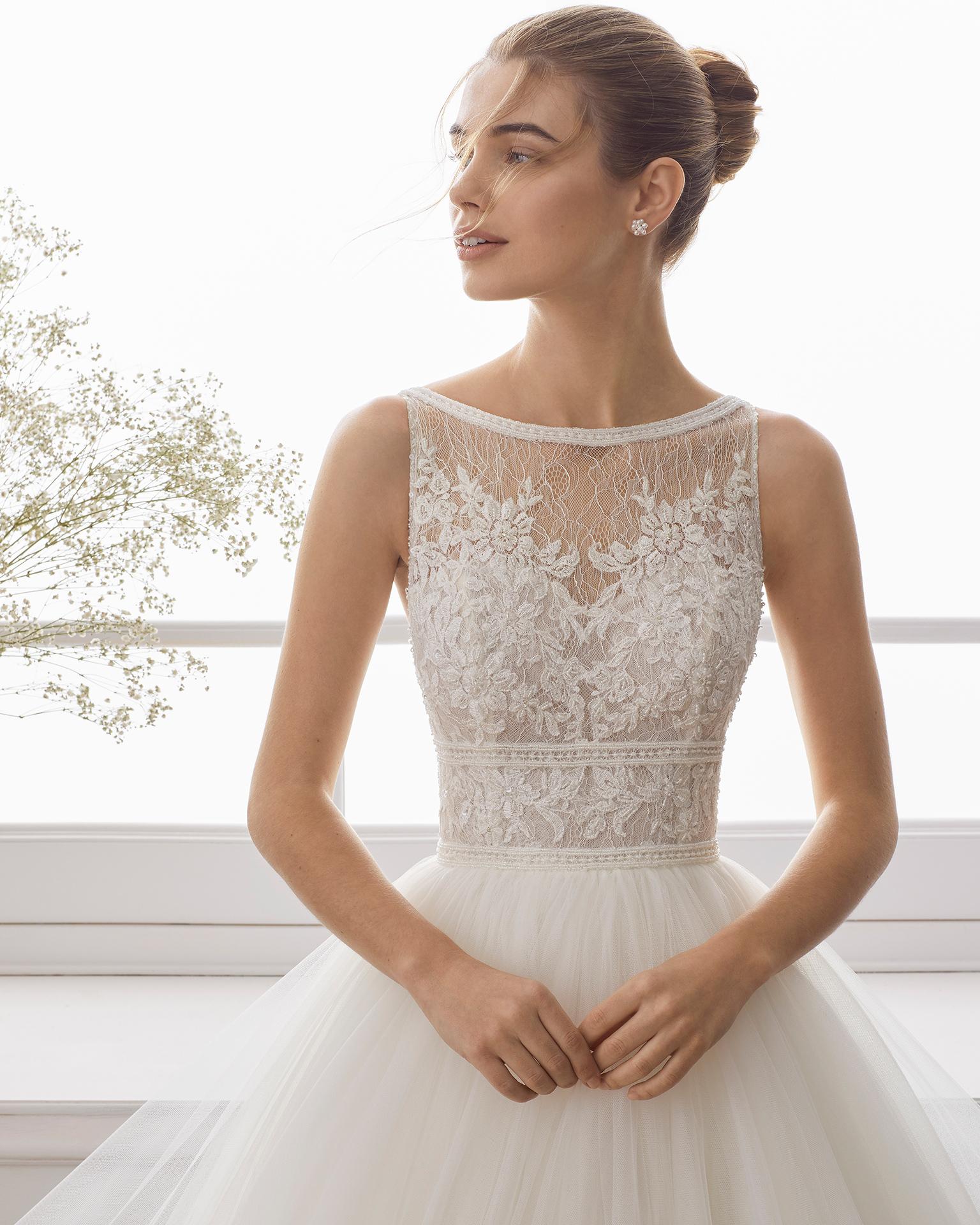 Vestido de noiva estilo princesa de renda de brilhantes e tule suave. Decote à barco e costas decotadas. Disponível em cor marfim. Coleção AIRE BARCELONA 2019.