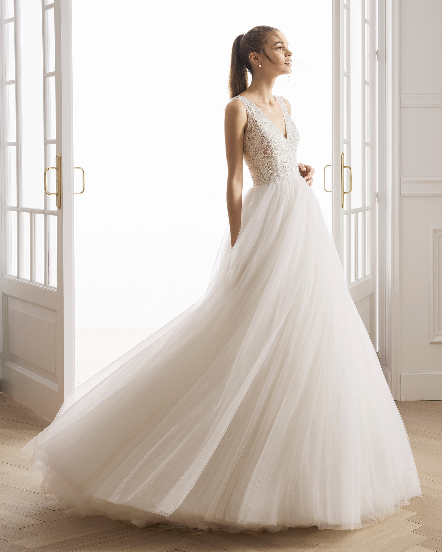 Vestido de noiva estilo princesa de renda, brilhantes e tule. Decote em V e costas decotadas. Disponível em cor marfim. Coleção AIRE BARCELONA 2019.