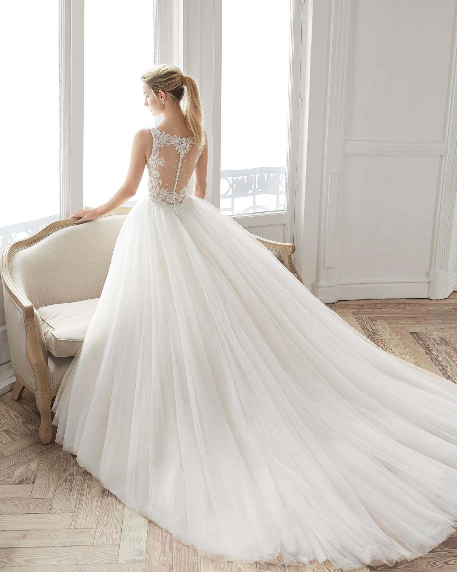 Vestido de noiva estilo princesa de renda, brilhantes e tule. Decote em V e costas de renda. Disponível em cor natural. Coleção AIRE BARCELONA 2019.