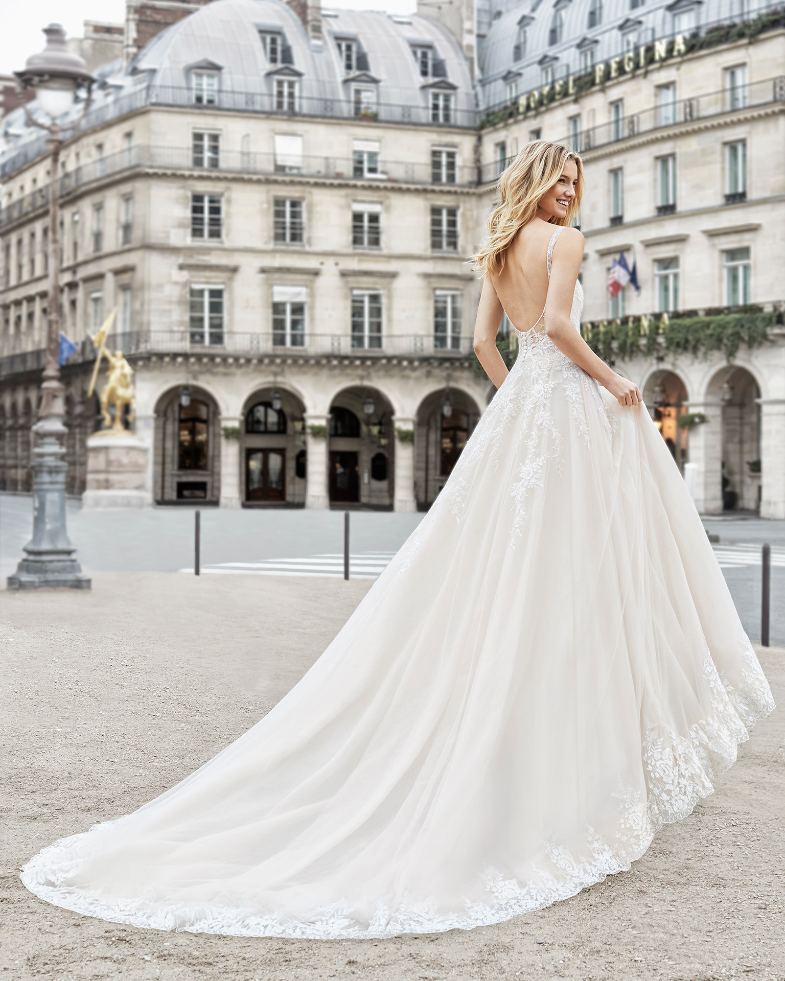 Robe de mariée style princesse en dentelle et tulle royal. Col en V et décolleté dans le dos. Disponible en couleur ambre, blanche légèrement grisâtre, et naturelle. Collection AIRE BARCELONA 2019.
