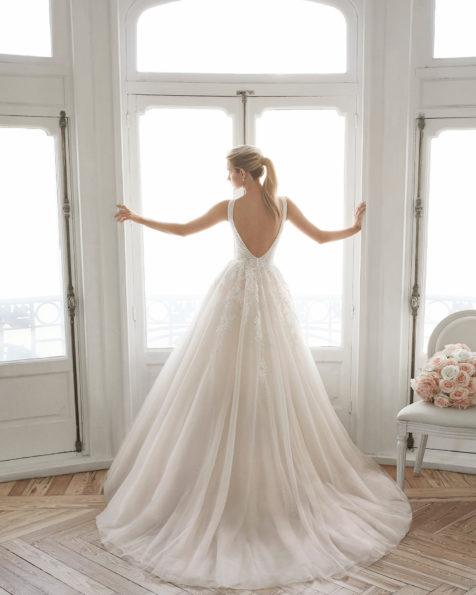 Romantisches Brautkleid aus Spitze und Royal-Tüll. Deep-Plunge-Ausschnitt und tief ausgeschnittener Rücken. Erhältlich in Bernstein, Eisgrau und Naturweiß. Kollektion AIRE BARCELONA 2019.