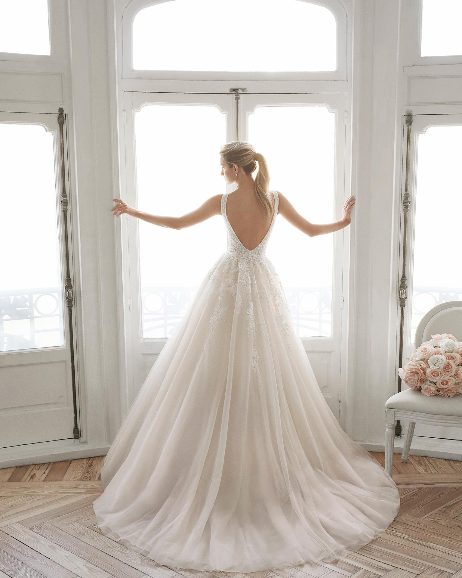 Vestido de noiva estilo romântico de renda e tule real. Decote deep-plunge e costas decotadas. Disponível em âmbar, azul-gelo e cor natural. Coleção AIRE BARCELONA 2019.
