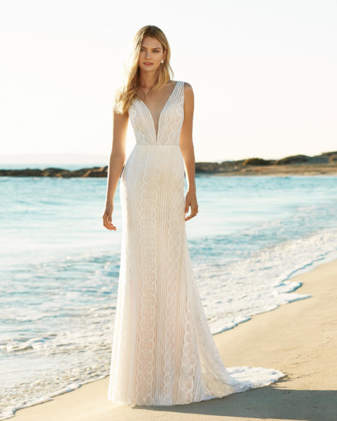 Mermaid-style wedding dress in beaded lace. Deep-plunge neckline and low back. Available in natural/nude. 2019 AIRE BEACH WEDDING Collection.