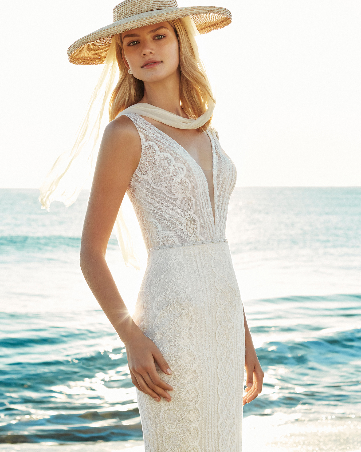 Robe de mariée coupe sirène en dentelle et pierreries. Décolleté plongeant et décolleté dans le dos. Disponible en couleur naturelle/nude. Collection AIRE BEACH WEDDING 2019.