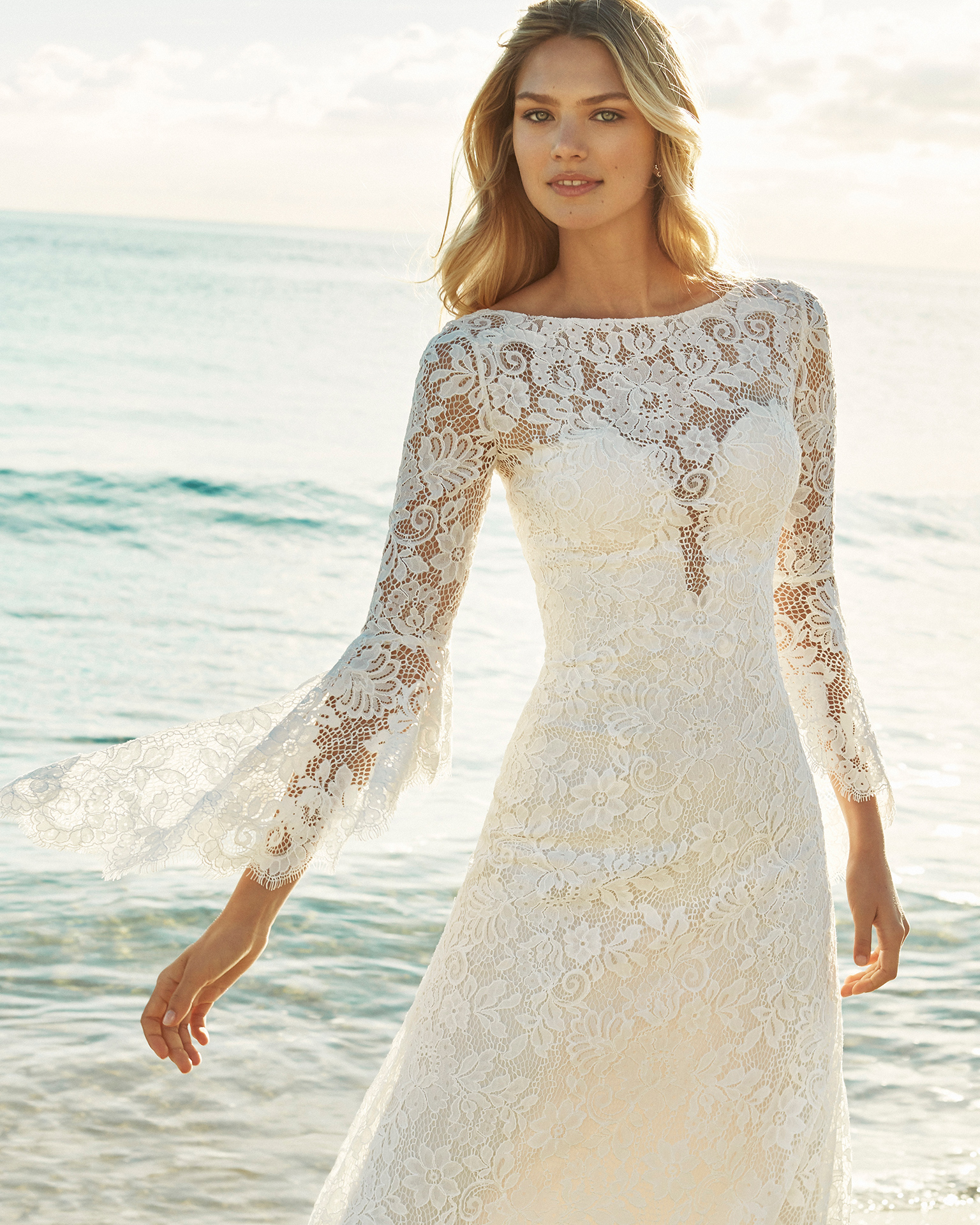 Robe de mariée coupe droite en dentelle.  Col bateau avec manches longues évasées et décolleté dans le dos. Disponible en couleur naturelle. Collection AIRE BEACH WEDDING 2019.
