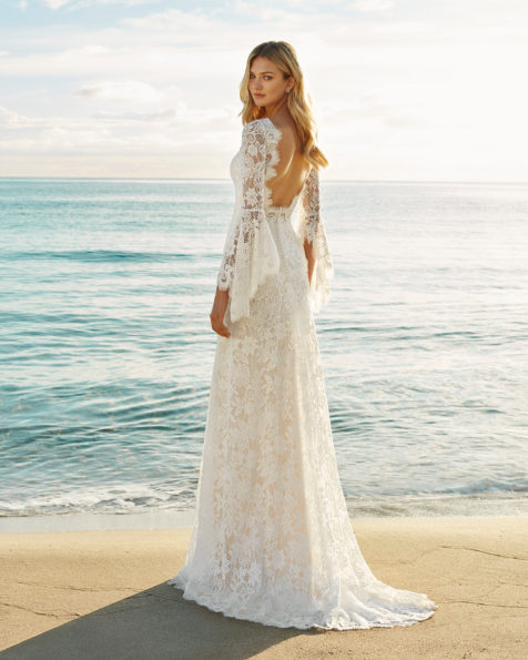 Sheath-style lace wedding dress.  Bateau neckline with long bell sleeves and low back. Available in natural. 2019 AIRE BEACH WEDDING Collection.