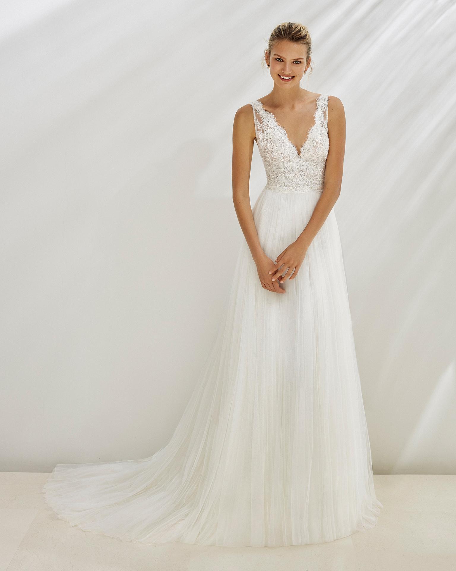 Vestido de noiva estilo linha A de tule suave e renda de brilhantes. Decote em V. Disponível em cor natural. Coleção AIRE BEACH WEDDING 2019.