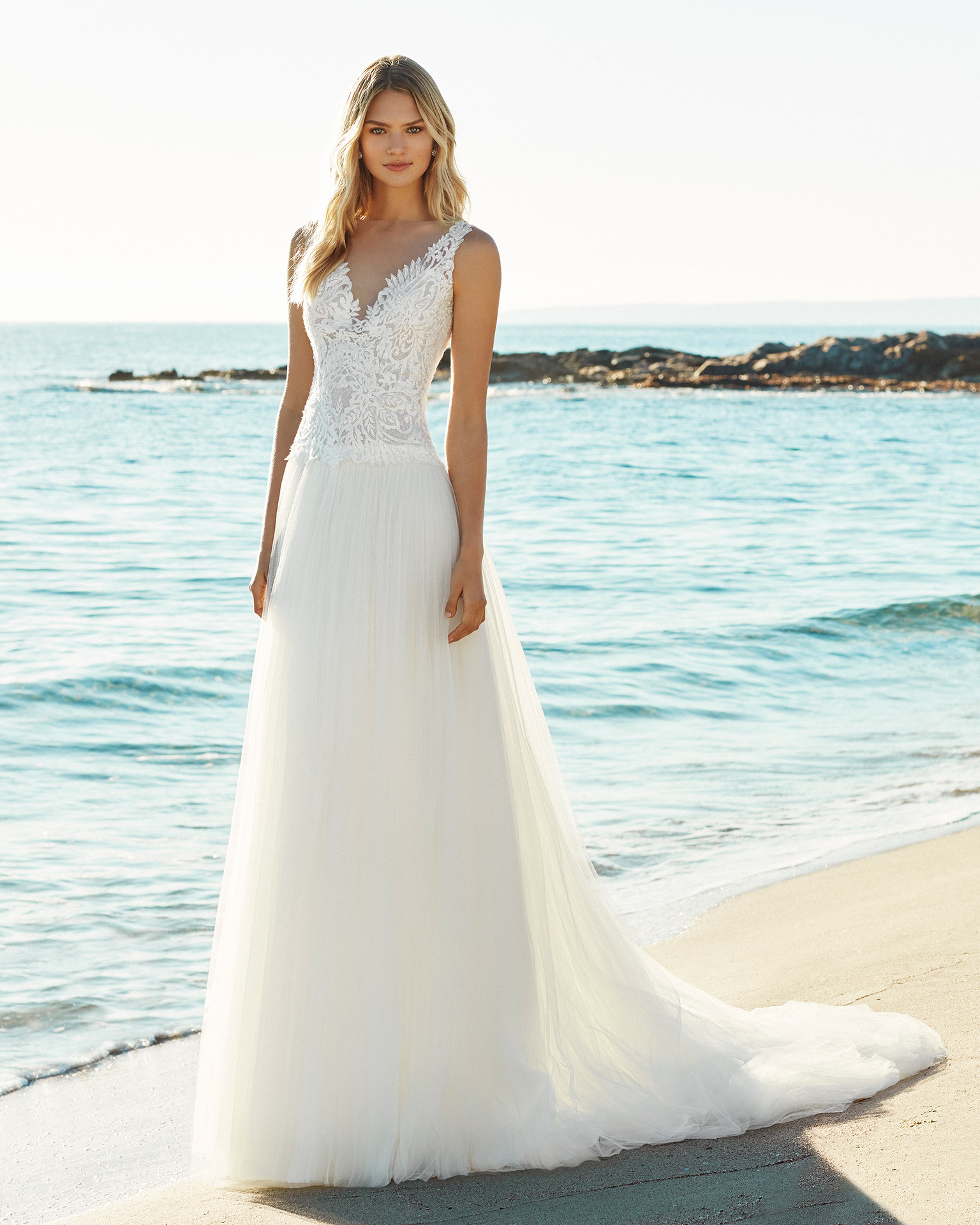 A-line beaded lace and soft tulle wedding dress. V-neckline and low back. Available in natural. 2019 AIRE BEACH WEDDING Collection.
