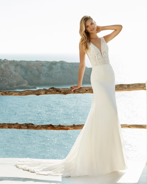 Sheath-style wedding dress in chiffon and beaded lace. Deep-plunge neckline and low back. Available in natural. 2019 AIRE BEACH WEDDING Collection.