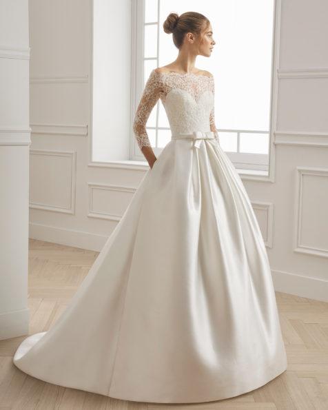 经典款塔米珠饰蕾丝新娘礼服。一字领长袖配腰部蝴蝶结设计。 有米白色可选。 AIRE BARCELONA 新品系列 2019.