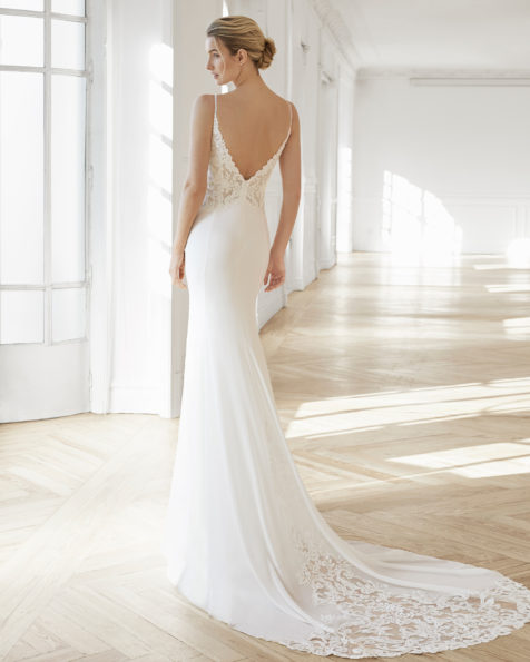 Sheath-style wedding dress in crepe Georgette and lace. V-neckline with chiffon and lace cape and V-back with beaded    neckline. Available in n                                    atural. 2019 AIRE BARCELONA Collection.