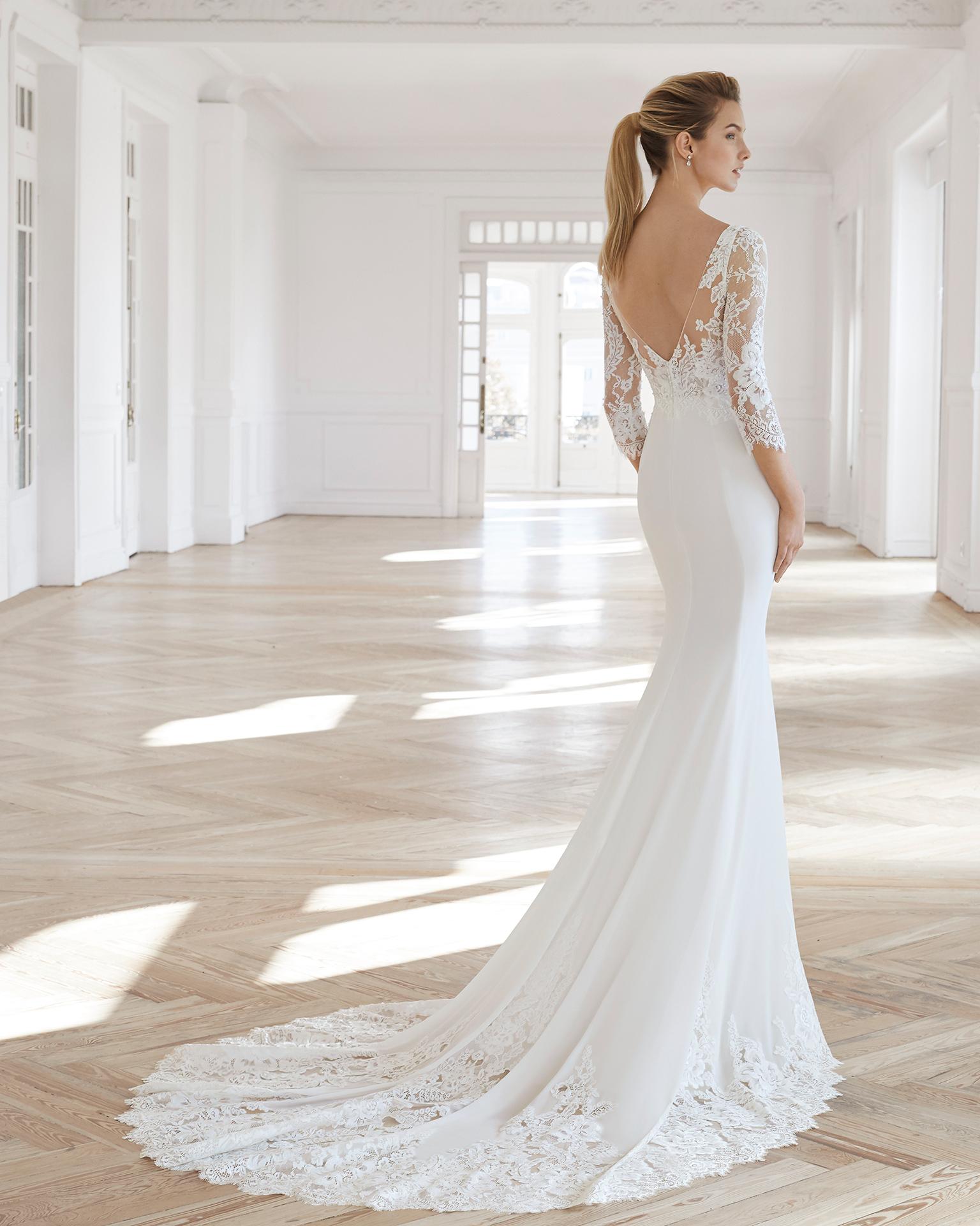 Vestido de noiva corte reto de crepe georgete e renda de brilhantes. Decote ilusão e manga comprida. Disponível em cor natural. Coleção AIRE BARCELONA 2019.