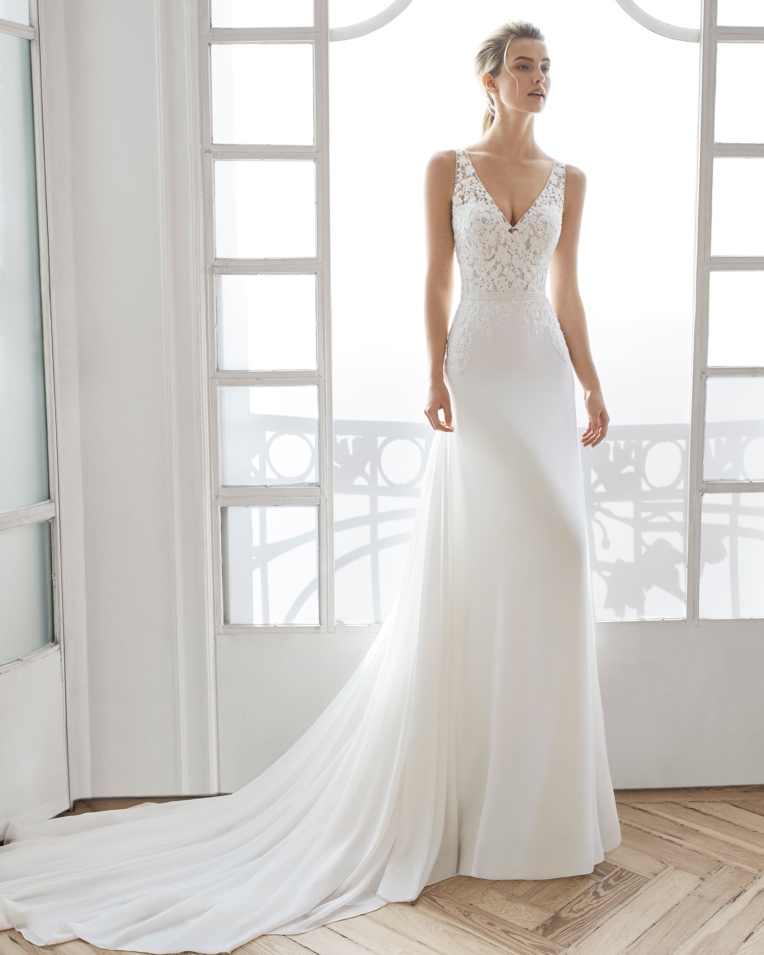 Sheath-style wedding dress in beaded lace and chiffon. V-neckline with beaded straps and lace back. Available in natural. 2019 AIRE BARCELONA Collection.