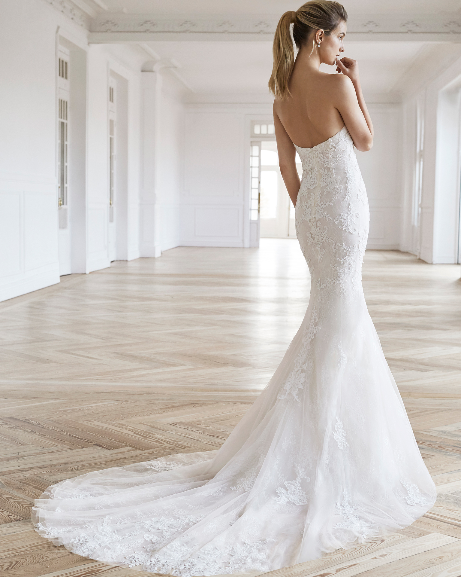 Mermaid-style wedding dress in beaded lace. Strapless neckline and beaded lace and tulle cape. Available in natural/nude and natural. 2019 AIRE BARCELONA Collection.