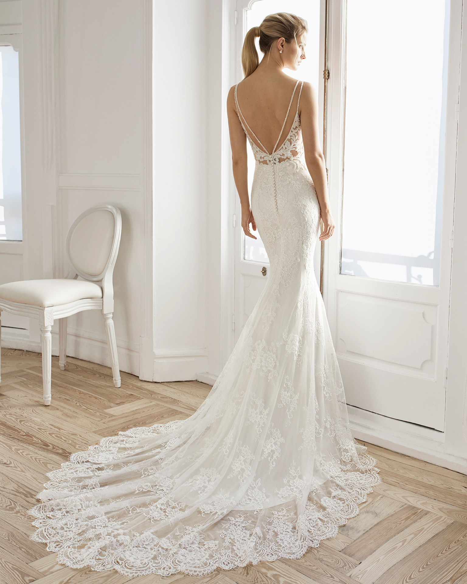 Mermaid-style wedding dress in beaded lace. Deep-plunge neckline with beaded straps and low back. Available in natural. 2019 AIRE BARCELONA Collection.