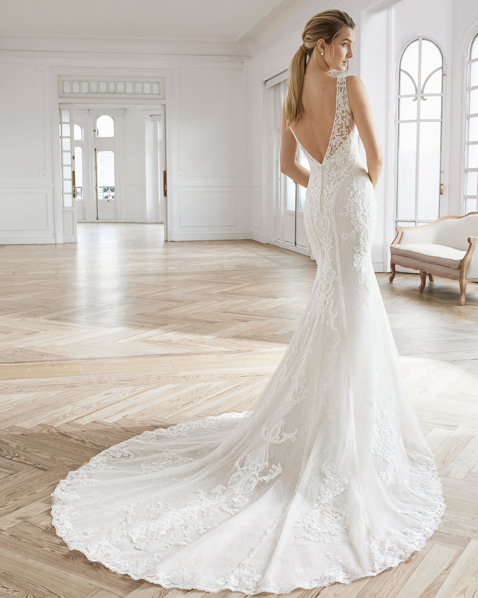 Mermaid-style wedding dress in beaded lace. V-neckline with draped lace and tulle and V-back. Available in natural/rose and natural. 2019 AIRE BARCELONA Collection.