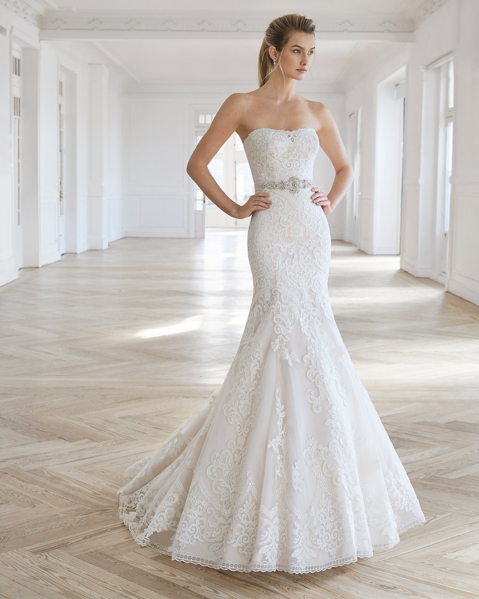Sheath-style wedding dress in beaded lace. Strapless neckline, back with bow at rear and beaded belt. Available in ivory and natural/champagne. 2019 AIRE BARCELONA Collection.