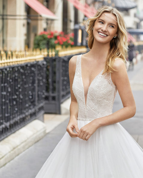 Princess-style wedding dress in beaded tulle. Deep-plunge neckline and V-back. Available in natural. 2019 AIRE BARCELONA Collection.