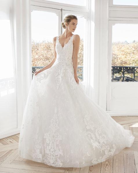 Romantisches Brautkleid aus Spitze und Tüll. V-Ausschnitt vorne und am Rücken. Erhältlich in Naturweiß. Kollektion AIRE BARCELONA 2019.