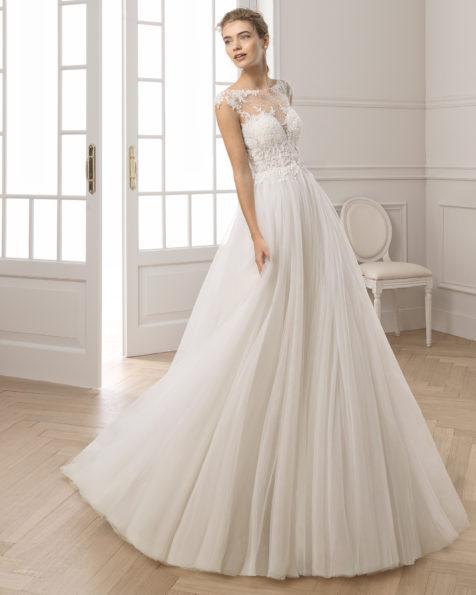 Princess-Brautkleid aus strassbesetzter Spitze und Tüll. U-Boot-Ausschnitt und kurze Ärmel. Erhältlich in Naturweiß. Kollektion AIRE BARCELONA 2019.