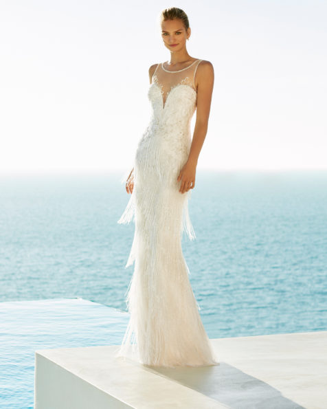 Sheath-style beaded lace wedding dress. Illusion neckline and fringe. Available in natural/silver and natural. 2019 AIRE BEACH WEDDING Collection.