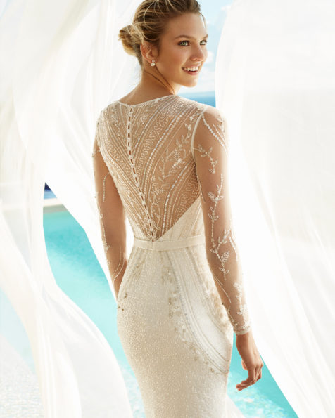Vestido de novia corte recto en pedrería. Escote deep-plunge y manga larga. Disponible en color natural/plata y natural. Colección AIRE BEACH WEDDING 2019.