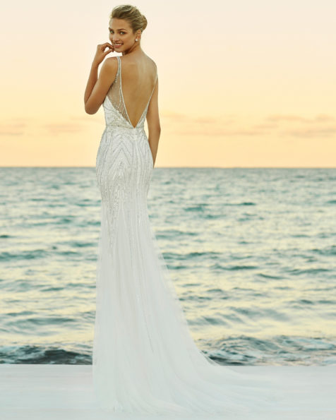Beaded mermaid-style wedding dress. Deep-plunge neckline and low back. Available in natural/silver and natural. 2019 AIRE BEACH WEDDING Collection.