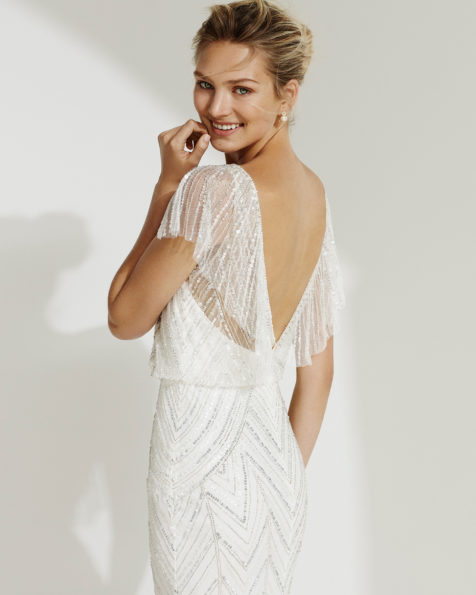 Beaded sheath-style wedding dress. Illusion neckline and short sleeves with low back. Available in natural/silver and natural. 2019 AIRE BEACH WEDDING Collection.