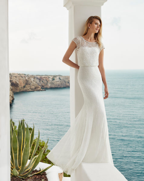 Beaded mermaid-style wedding dress. Deep-plunge neckline, short sleeves and low back. Available in natural and silver. 2019 AIRE BEACH WEDDING Collection.