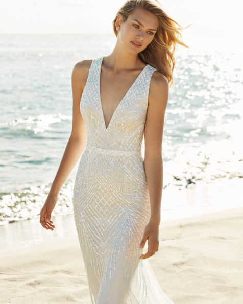 Vestido de novia corte sirena en pedrería. Escote deep-plunge y espalda escotada. Disponible en color natural. Colección AIRE BEACH WEDDING 2019.