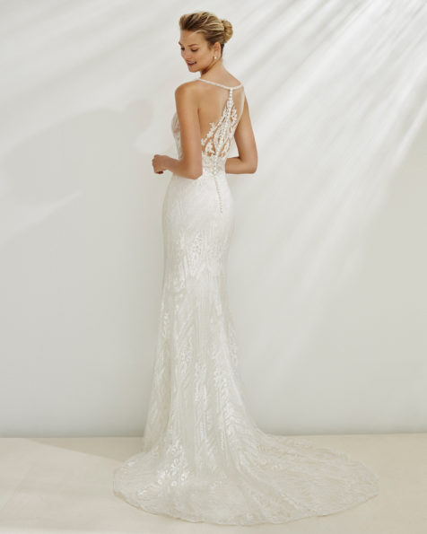 Mermaid-style wedding dress in beaded lace. Deep-plunge neckline with sheer inserts on the back. Available in natural. 2019 AIRE BEACH WEDDING Collection.