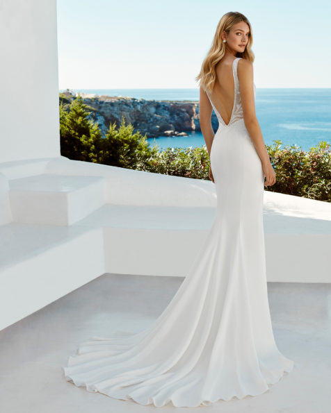 Sheath-style wedding dress in beaded crepe. V-neckline and low back. Available in natural. 2019 AIRE BEACH WEDDING Collection.