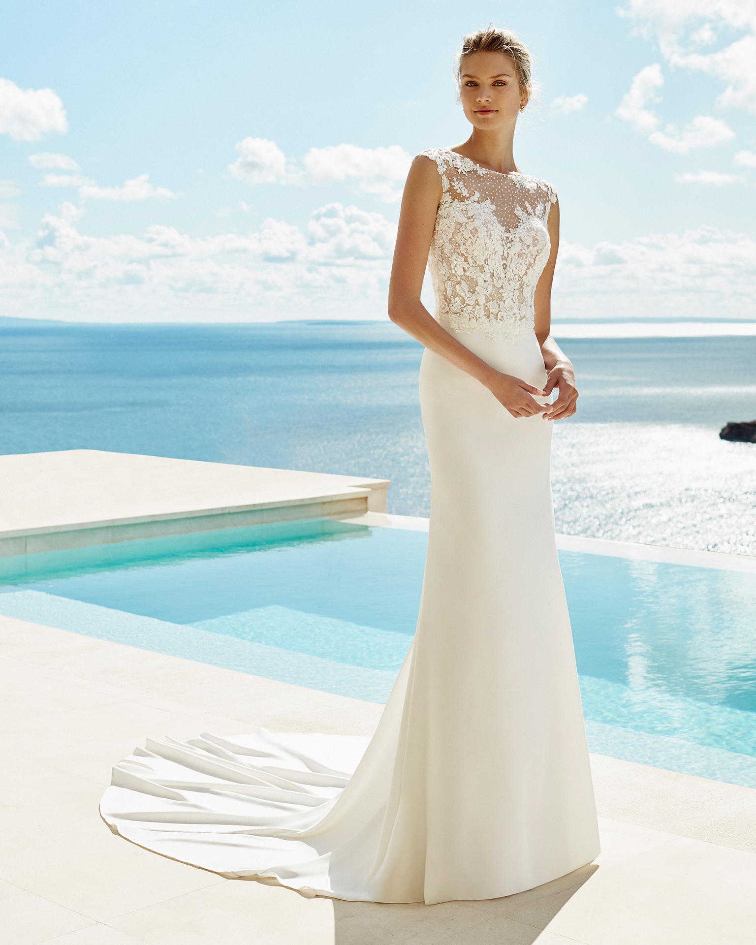Sheath-style wedding dress in crepe and beaded lace. Bateau neckline and short sleeves. Available in natural. 2019 AIRE BEACH WEDDING Collection.