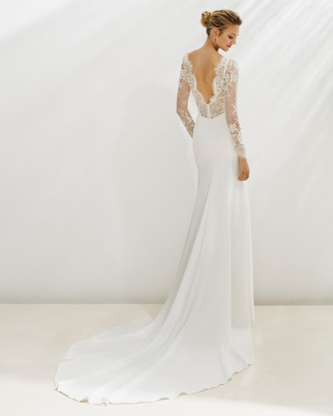 Sheath-style wedding dress in crepe and beaded lace. Bateau neckline and long sleeves. Available in natural. 2019 AIRE BEACH WEDDING Collection.