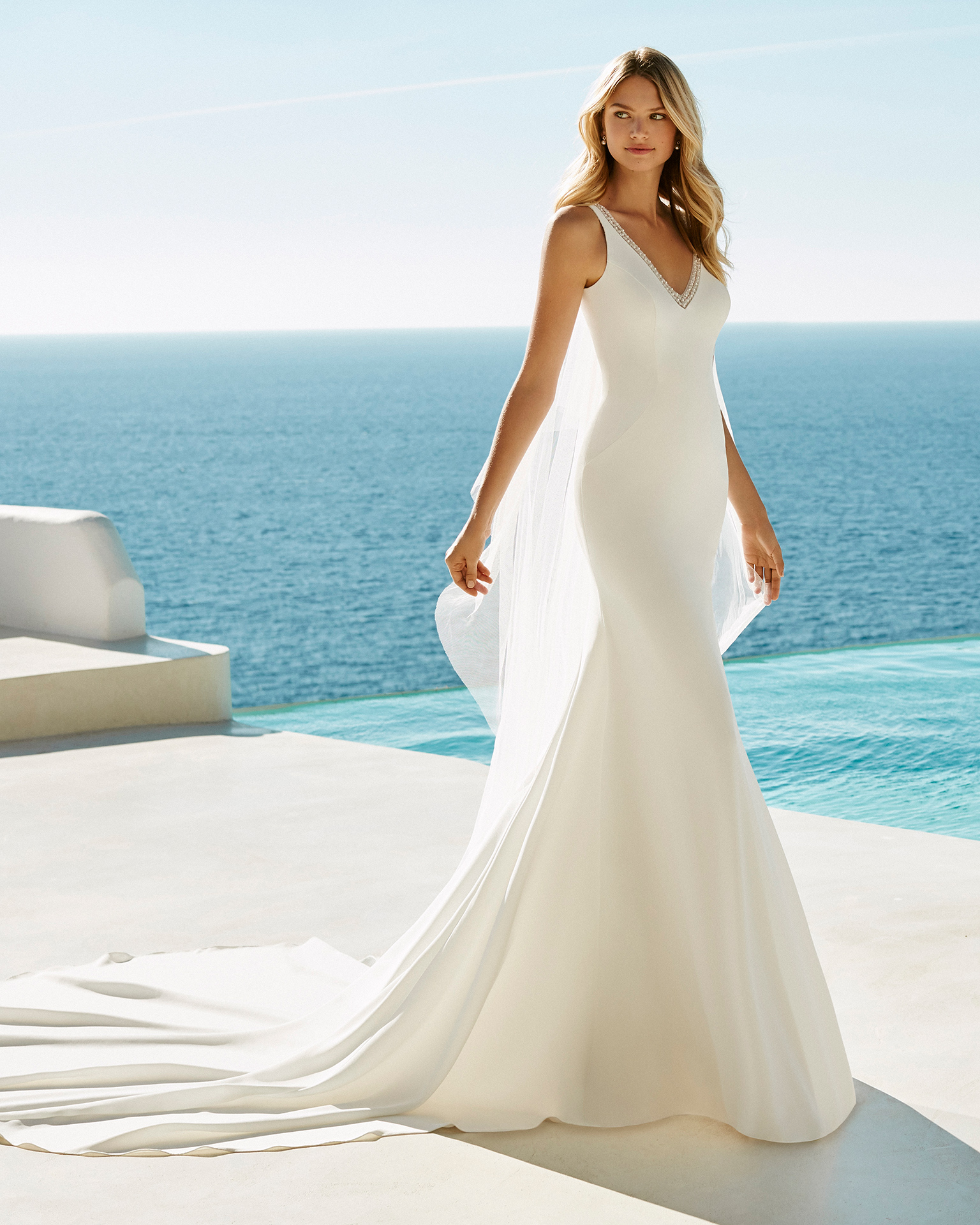 Sheath-style wedding dress in crepe and beaded lace. V-neckline and lace back. Available in natural. 2019 AIRE BEACH WEDDING Collection.