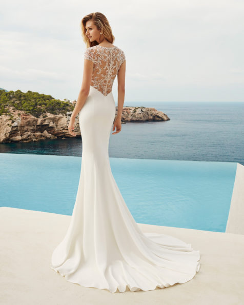Sheath-style wedding dress in beaded crepe. Bateau neckline, short sleeves and back with sheer inserts. Available in natural and natural/rose. 2019 AIRE BEACH WEDDING Collection.