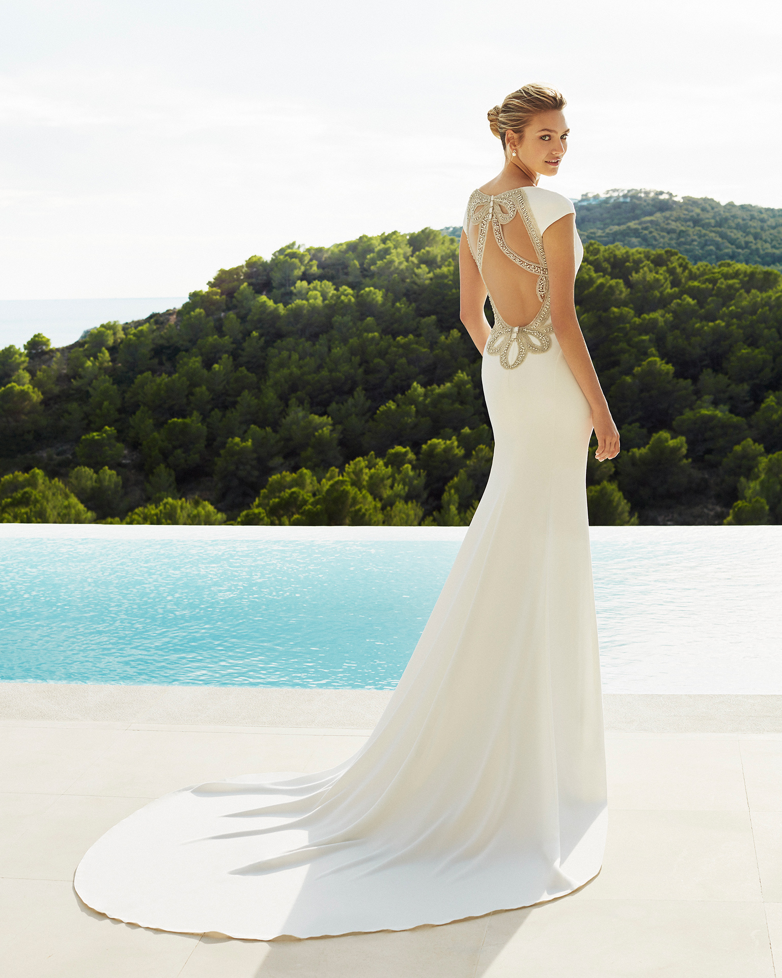 Sheath-style wedding dress in beaded crepe. Round neckline, short sleeves and jewelled back. Available in natural. 2019 AIRE BEACH WEDDING Collection.